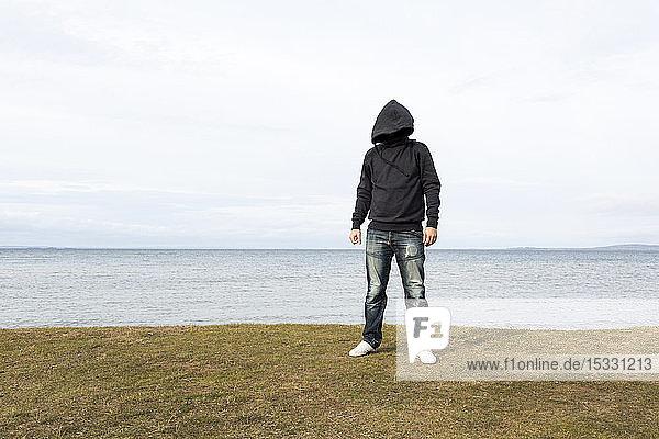 Kapuzenmann am See stehend