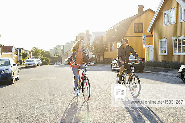 Couple cycling on suburban street