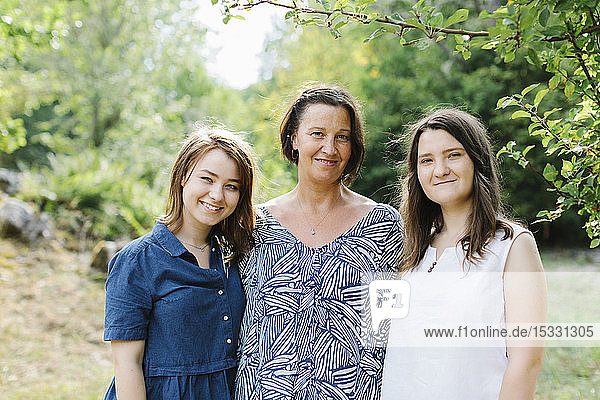Portrait of mother and daughters in forest