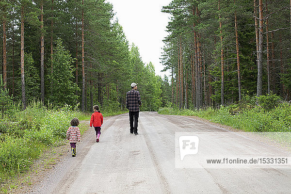 Man and children walking on rural road through forest
