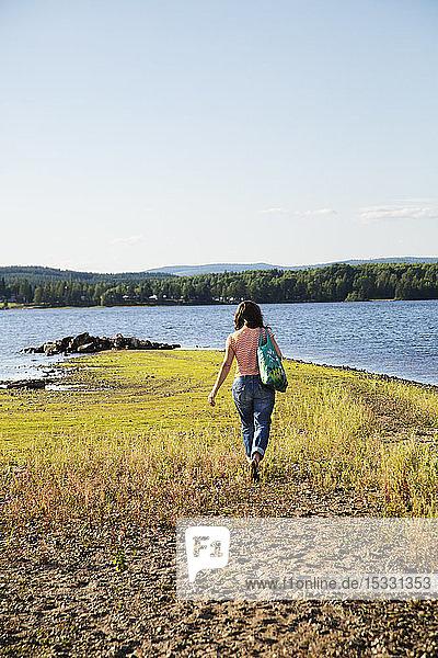 Woman walking by lake Woman walking by lake