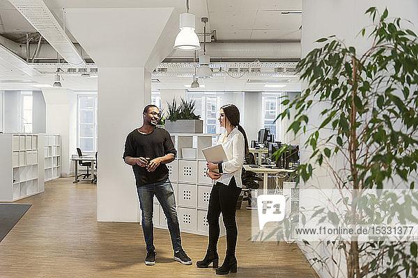 Coworkers talking in office