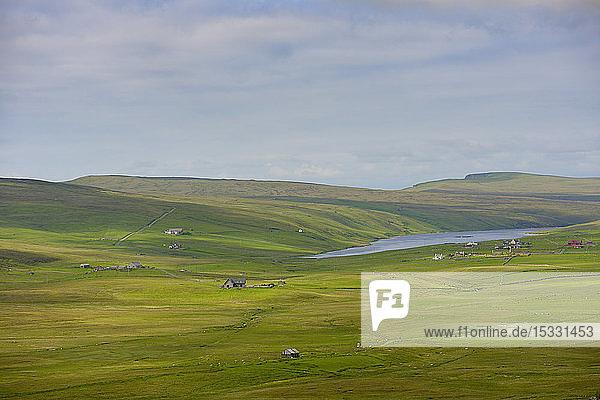 Grüne Ebene und entferntes Meer auf den Shetlandinseln  Vereinigtes Königreich