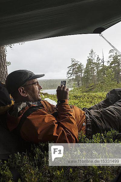 Mann benutzt Smartphone im Zelt