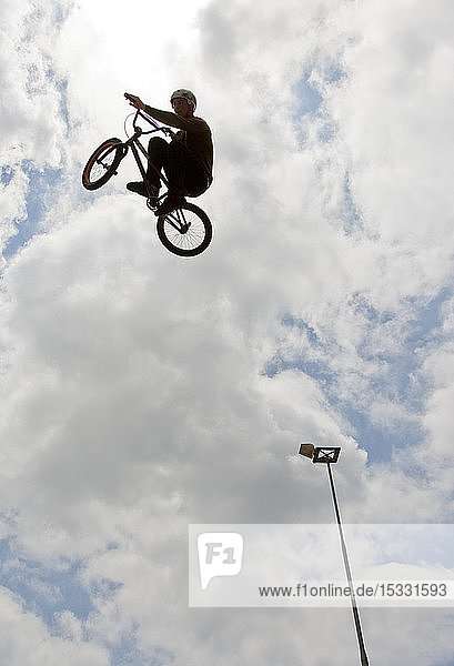 Side view of man doing bmx trick