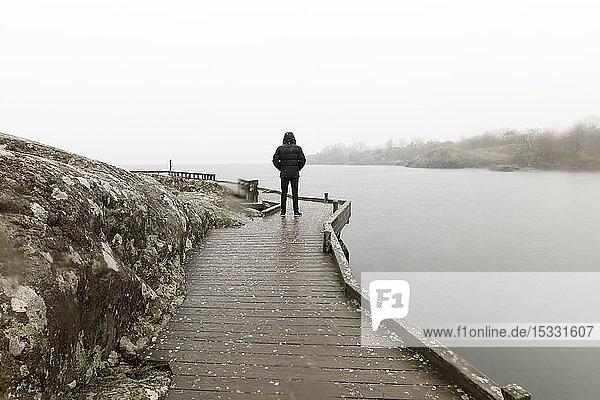 Mann auf Uferpromenade am See