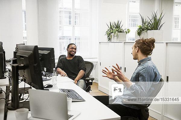 Gespräche zwischen Kollegen am Schreibtisch