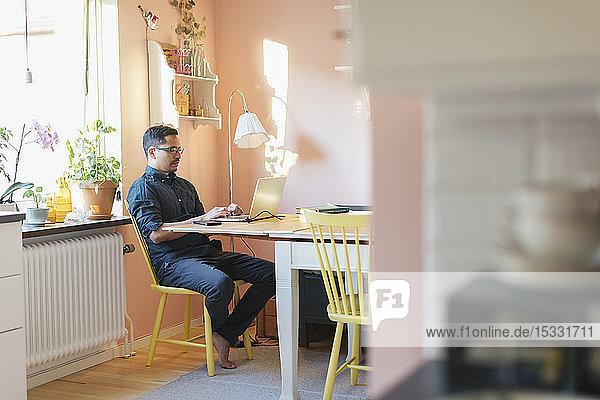 Man using laptop at dining table
