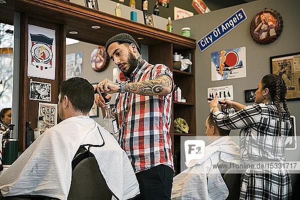 Barbers cutting customer´s hair