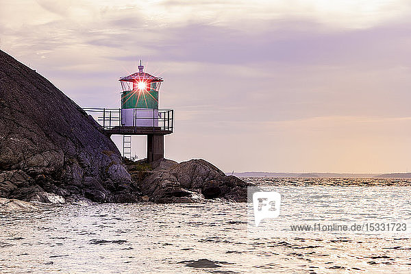 Lighthouse on rocks by sea during sunset in Kanholm Bay  Sweden