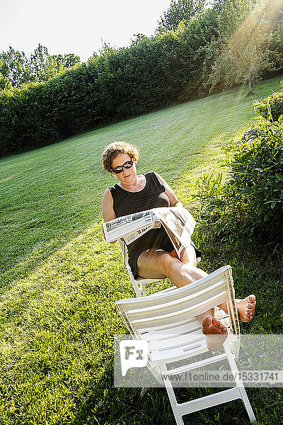Woman sitting on chair and reading newspaper on sunny day