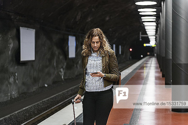 Young woman with suitcase at subway station