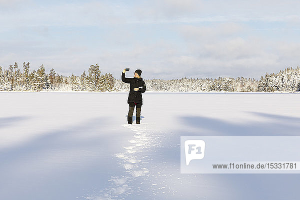 Woman taking photograph with smart phone on snow covered Stora Skiren lake in Lotorp  Sweden