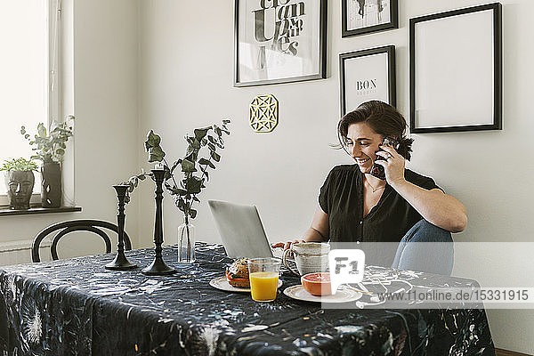 Young woman using laptop and smart phone during breakfast