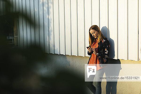 Junge Frau benutzt Smartphone an der Wand