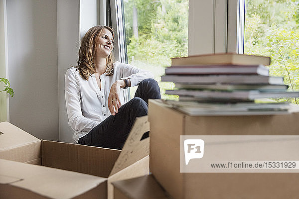Woman sitting on window sill behind cardboard boxes