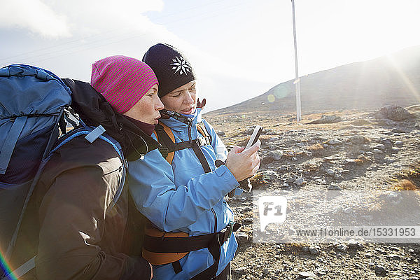 Women using smart phone during hike