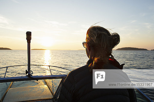 Woman on boat at sunset