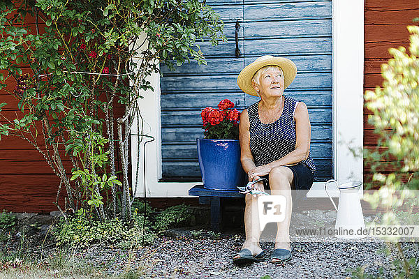 Senior woman sitting by flower pot in front of door