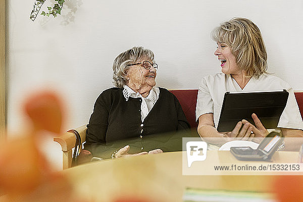 Senior woman learning to use tablet PC
