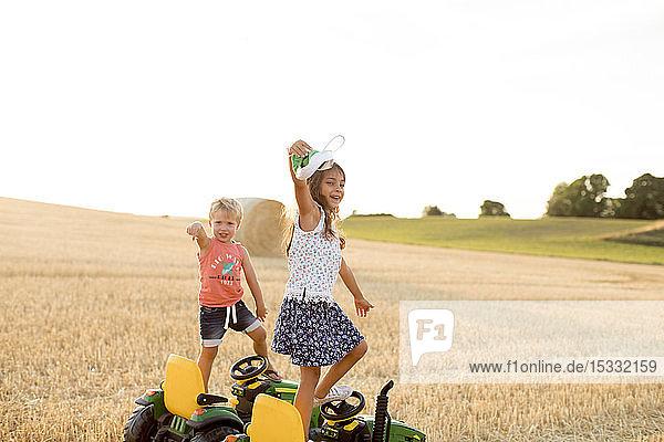 Kinder stehen auf Spielzeugtraktoren in einem Feld