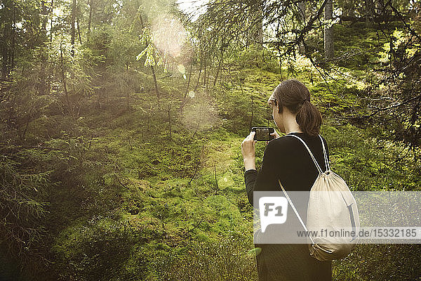 Woman taking photograph in forest