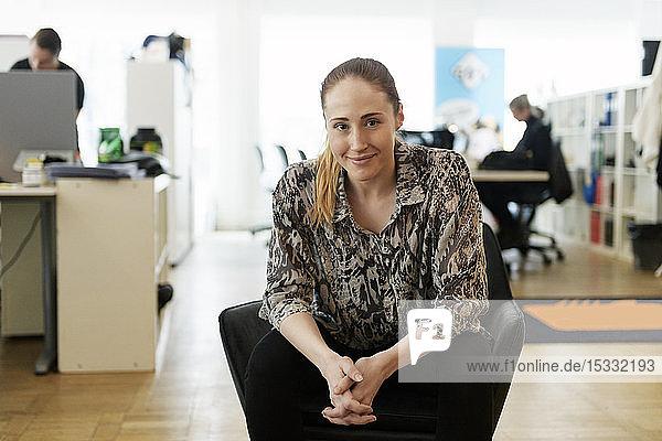 Portrait of businesswoman sitting in armchair