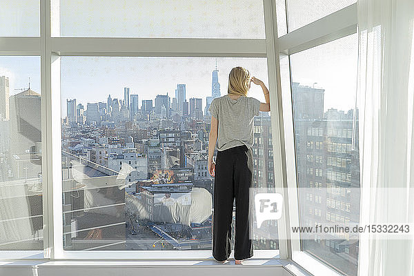 Teenage girl shielding eyes in front of city apartment window