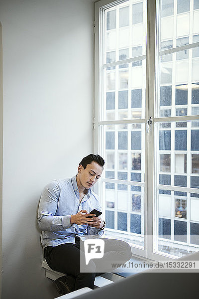 Young man using smart phone by window Young man using smart phone by window