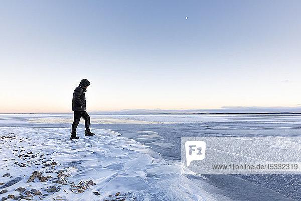 Mann  der bei Sonnenuntergang auf dem zugefrorenen Glan-See in Ostergotland  Schweden  spazieren geht