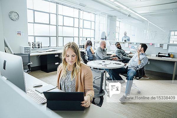 Woman using digital tablet in office