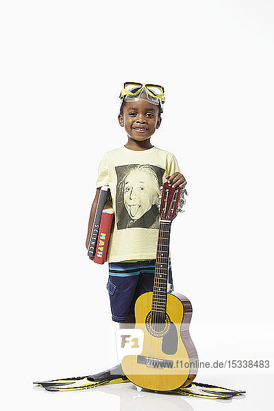 Boy wearing Einstein t-shirt and scuba mask holding guitar and books