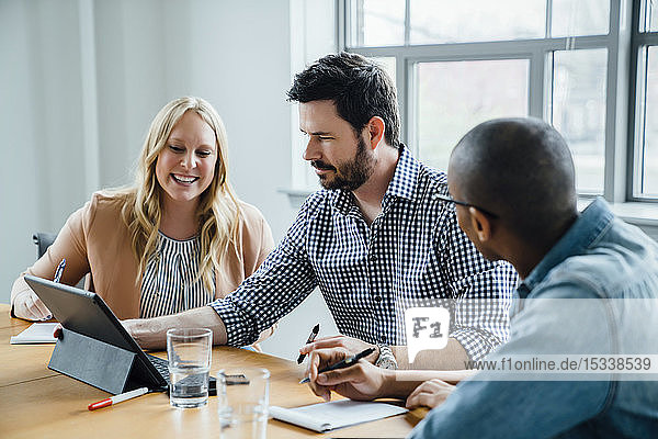 Coworkers using digital tablet in board room