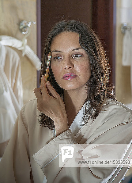 Woman wearing bathrobe applying eyeshadow