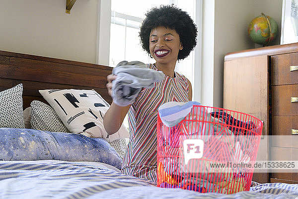 Smiling young woman doing laundry on bed