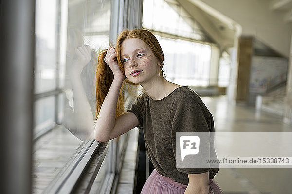 Redhead young woman leaning against window