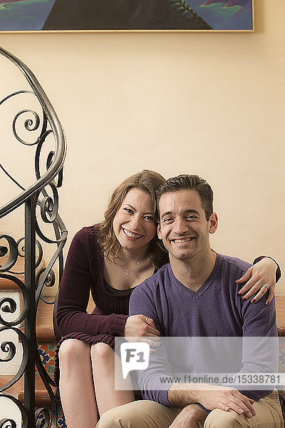 Smiling young couple sitting on staircase