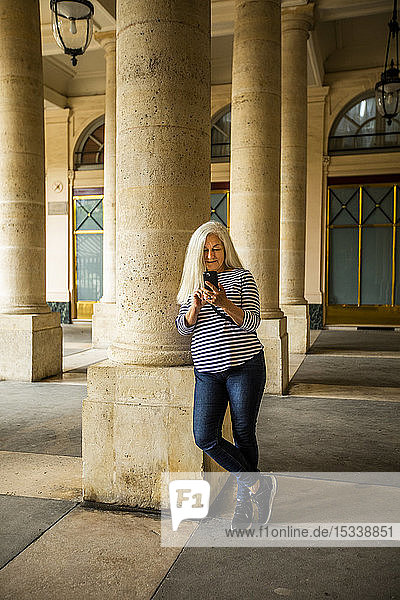 Woman using smart phone by columns of Palais-Royal in Paris  France