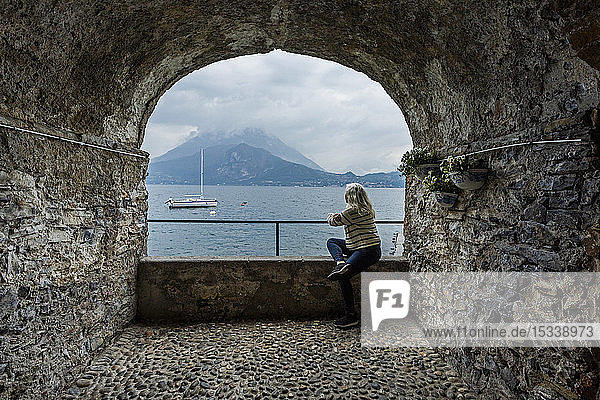 Woman sitting under arch by Lake Como  Italy
