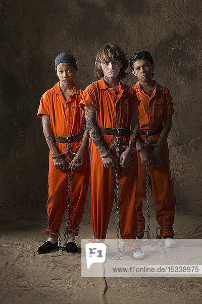 Boys in prisoner jumpsuits and handcuffs