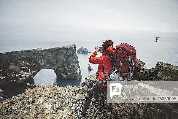 Female hiker photographing natural arch in Vik  Iceland