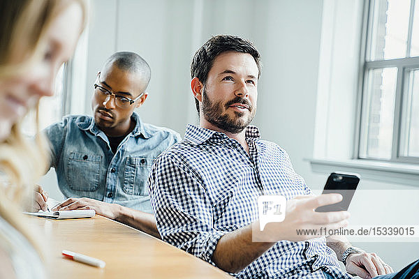 Man holding smart phone during meeting