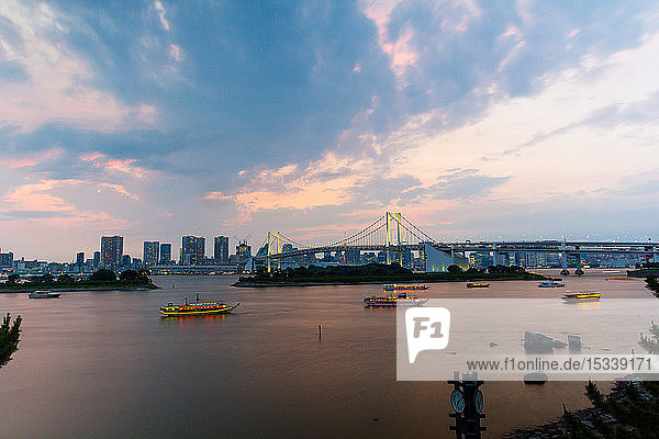 Rainbow bridge with Tokyo skyline at dusk