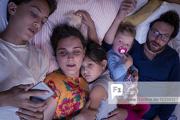 Family lying on bed at home