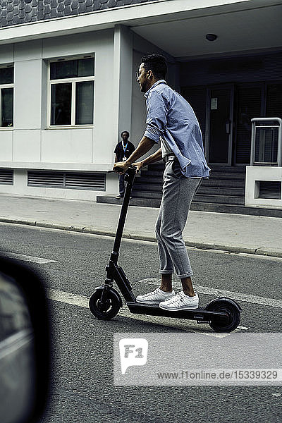 Young man riding push scooter
