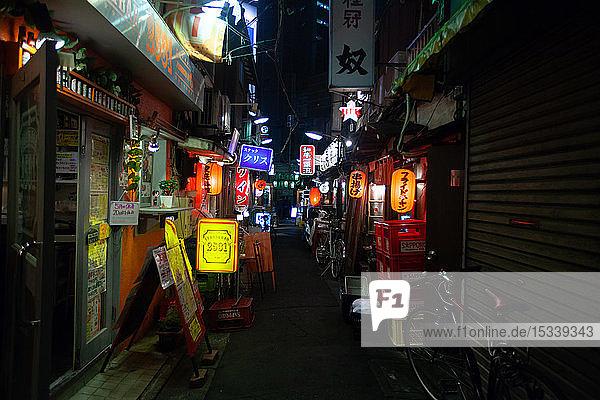 Illuminated signs of shops and bar at night