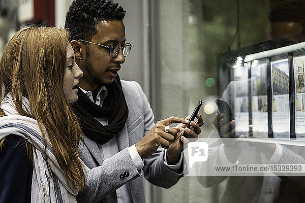 Couple using smartphone at window display