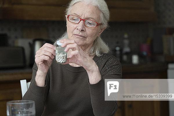 Woman reading label of pill bottle