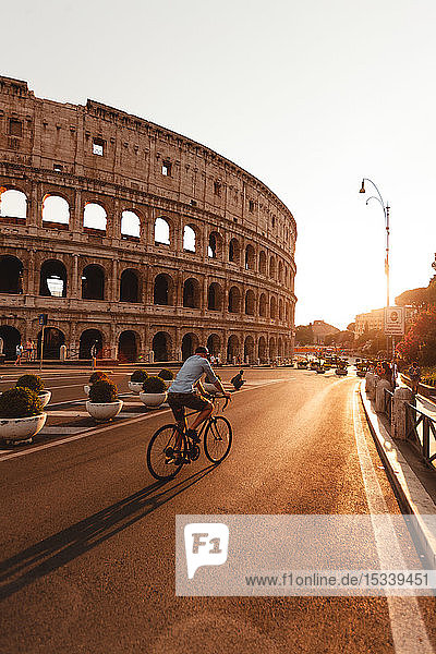 Man riding bicycle by Colosseum