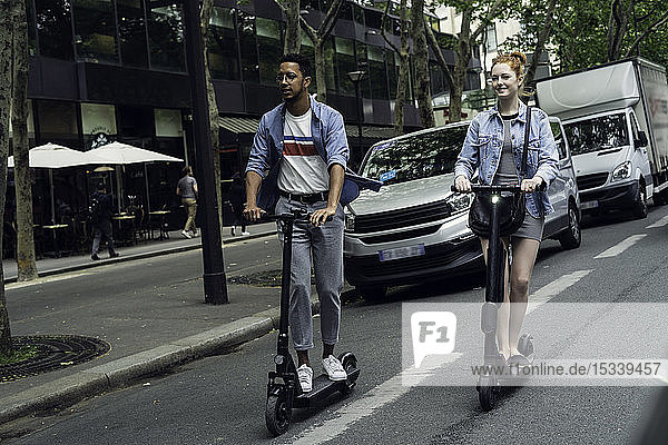 Couple riding push scooters